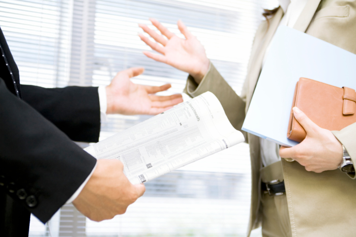 Businessman and businesswoman holding documents and talking